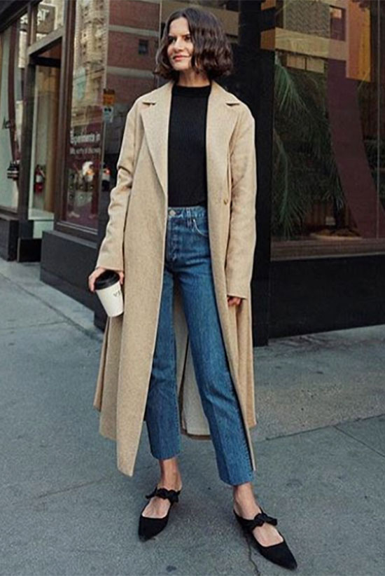 10 Simple Ways To Style A Long Coat: Fashion blogger 'Life Of Boheme' wearing a beige long coat, a black t-shirt, straight jeans and black mule heels.