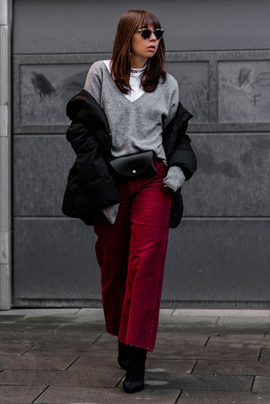 Sleek Ways To Style The Modern Fanny Pack: Fashion blogger 'SARAHVONH' wearing a black puffer jacket, a grey v-neck sweater over a white turtleneck top, red crop trousers, black sock boots and a black belt bag. Fanny pack, fanny pack outfit, belt bag, belt bag outfit, fashion trends 2018, fashion, fashion 2018, street style, casual outfit, winter outfit, puffer jacket outfit.