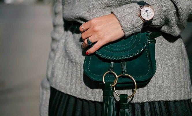Sleek Ways To Style The Modern Fanny Pack: Fashion blogger 'The Fashion Guitar' wearing a grey turtleneck sweater, a green pleated midi skirt and a green tassel bel bag. Fanny pack, fanny pack outfit, belt bag, belt bag outfit, fashion trends 2018, fashion, fashion 2018, street style, casual outfit, fall outfit.