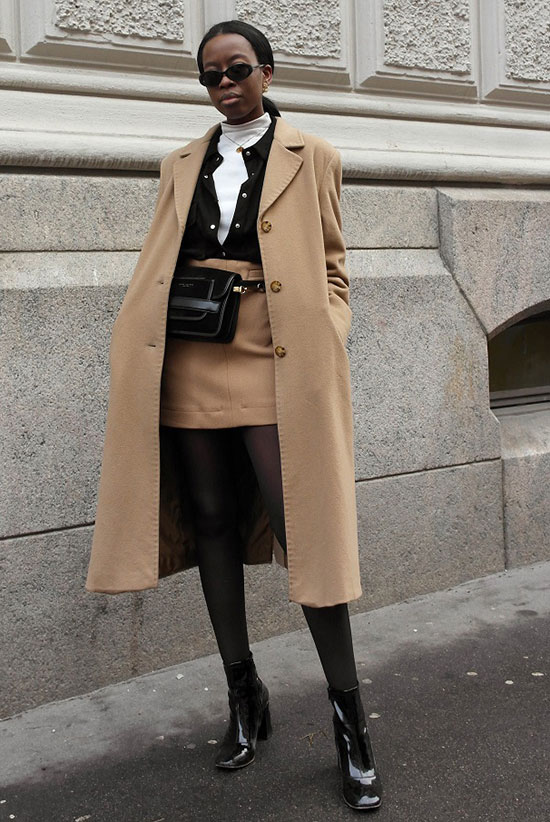 Sleek Ways To Style The Modern Fanny Pack: Fashion blogger 'Sylvie Mus' wearing a camel coat, a black shirt over a white turtleneck top, a camel midi skirt, black tights, black patent booties and a black belt bag. Fanny pack, fanny pack outfit, belt bag, belt bag outfit, fashion trends 2018, fashion, fashion 2018, street style, casual outfit, winter outfit, winter layers.