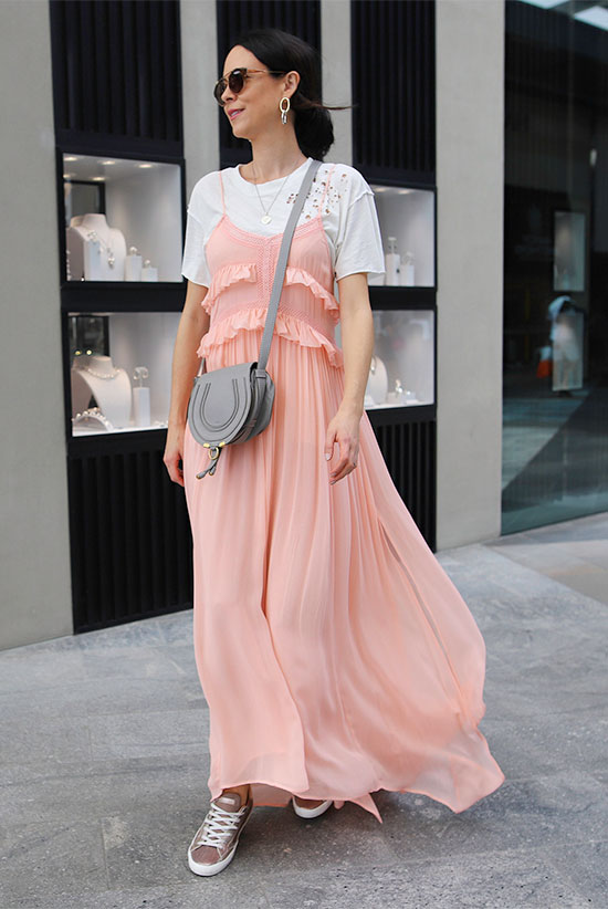 10 Chic Valentine's Outfits For Every Girls Style: Fashion blogger 'Fifi Deluxe' wearing a white distressed tee, a blush sleeveless maxi dress, grey sneakers, brown round sunglasses and a grey shoulder bag.