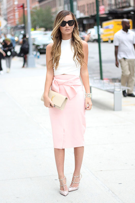 10 Chic Valentine's Outfits For Every Girls Style: Fashion blogger 'For All Things Lovely' wearing a white crop top, a pink pencil skirt, blush studded heels, black cat eye sunglasses and a beige clutch.