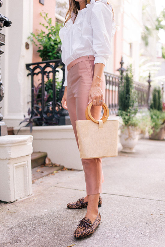 10 Chic Valentine's Outfits For Every Girls Style: Fashion blogger 'Gal Meets Glam' wearing a white ruffle blouse, blush ankle pants, leopard print loafers and a straw bag.