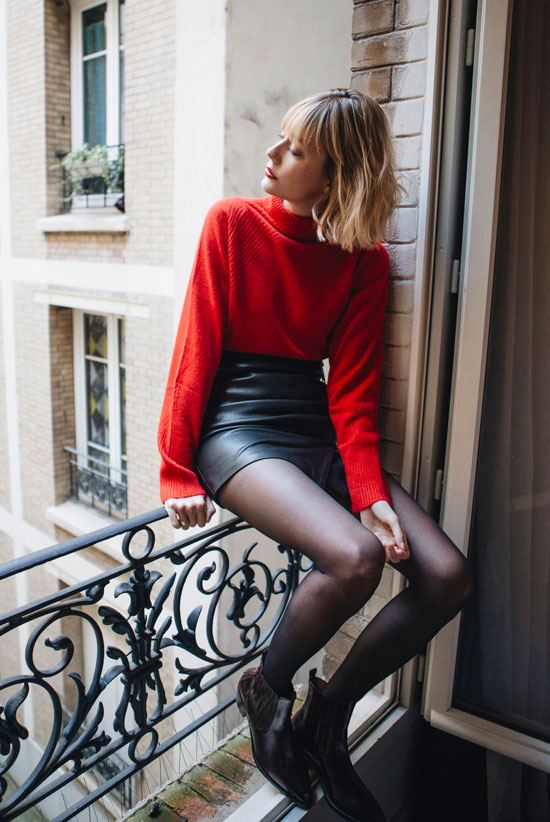 10 Chic Valentine's Outfits For Every Girls Style: Fashion blogger 'Into Your Closet' wearing a red turtleneck sweater, a black leather mini skirt, black tights and western booties.