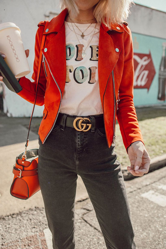 10 Chic Valentine's Outfits For Every Girls Style: Fashion blogger 'Jo & Kemp' wearing a red suede jacket, a white graphic t-shirt, black washed crop jeans, a black logo belt, white booties, round aviator sunglasses and a red shoulder bag.