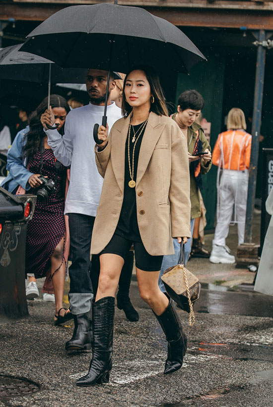 Chic Ways To Wear The Cowboy Boots Trend: Fashion blogger 'Song Of Style' wearing a camel blazer, a black t-shirt, black bike shorts, black cowboy boots and a brown clutch. fashion 2018, fall fashion trends, fall fashion, fall fashion trends 2018, street style, fall outfit, casual outfit, cowboy boots, cowboy boots trend, westernboots, nyfw 2018, #fashion2018, #casualstyle #fallstyle #fallfashion #cowgirl, #cowboyboots #westernboots #fashionweek #nyfw #nyfw2018 #streetstyle #bikeshorts #ootd